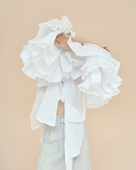 Model in plumes of white clothing, hiding face