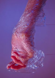 Hand wrapped with clingfilm against a purple background