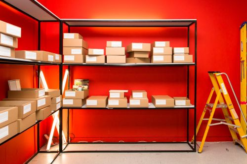 image of shelving units against orange wall with brown boxes with student work in. There's a yellow ladder to the right of the unit.