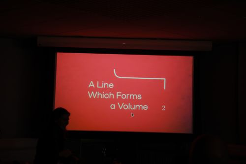 Red branding for A Line Which Forms A Volume projected onto the screen, with silhouettes.