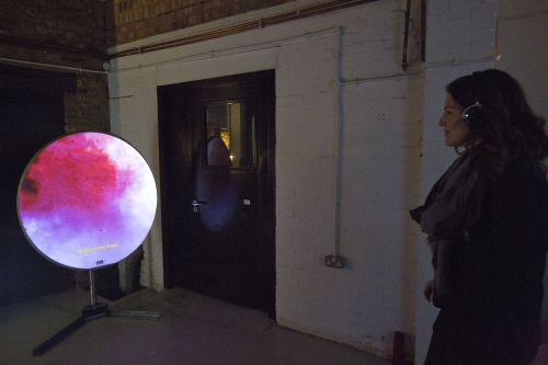 Person looking at pink and purple circle of projection