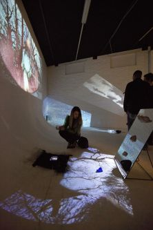 Two people standing in room of projected film