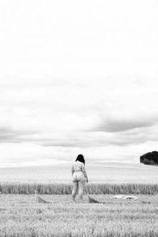 nude woman standing in field