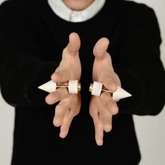 two spiked art objects being held between a persons index and middle finger with both hands