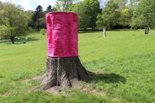 Pink sculpture sitting on tree stump