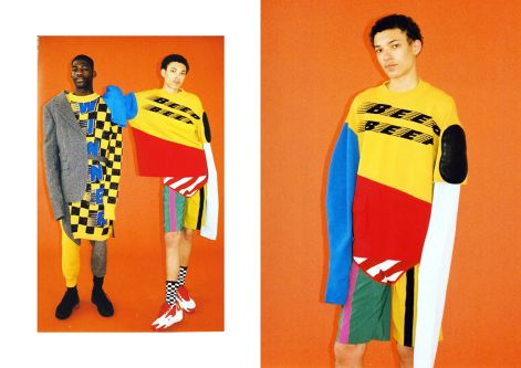 Two male models wearing oversized knits in yellow and black standing in front of an orange background