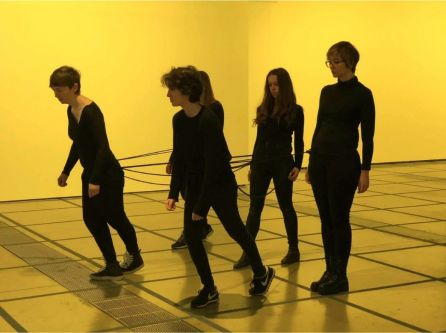 performance photo, women dressed in black in a yellow room