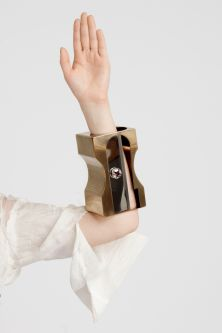 A model wearing a bracelet that resembles a large gold pencil sharpener