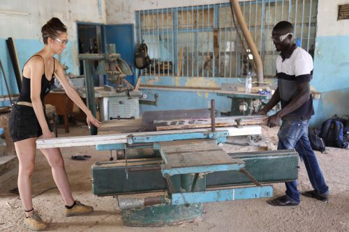 student being taught how to cut wood as part of Route-Artlantique project