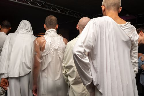 A line of male models with their backs turned all wearing white