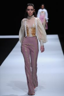 Female model wearing pink trousers and creamy blouse designed by Molly Lockley