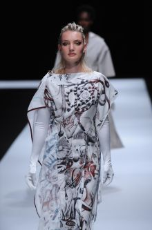Female model wearing long white and red embroided dress designed by Xinyi Zheng