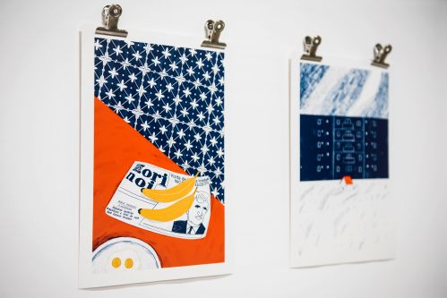 Two colourful prints fastened to a wall with bulldog clips