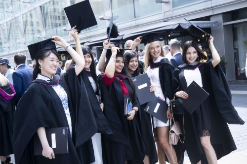 Six female graduates having a photograph and throwing their graduation hats in the air.