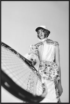 Black and white photograph of a model wearing a white hat and dress holding a tennis racket at the camera