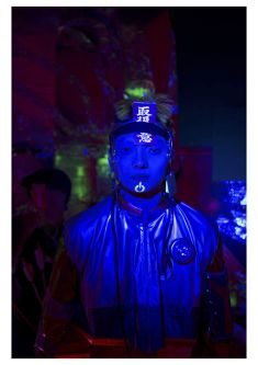Male model standing in the dark with a blue light