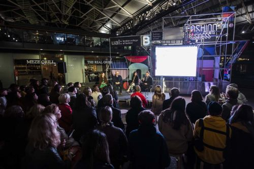 Audience sitting at Spitalfields market in front of a panel sitting in front of a neon sign saying 'Fashion Means Business'