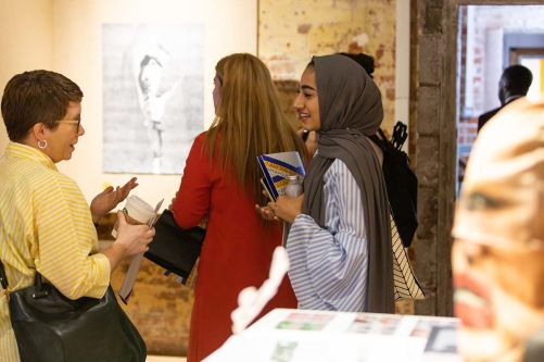 Smiling female prospective student wearing a hijab talking to a staff member at an exhibition