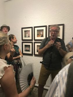 Image of david stewart talking about the photographs behind him in the gallery