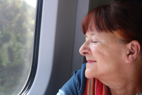 Lady gazing out the window of a train