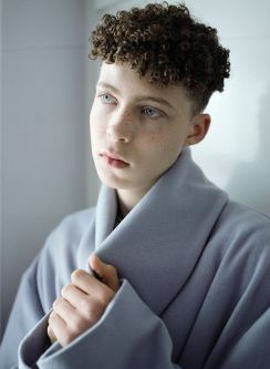 Model in grey jacket, cluthing the neck