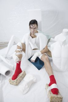 Male model sitting on the floor in red socks and foam shoes.