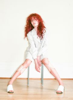 Model with red hair and legs splayed