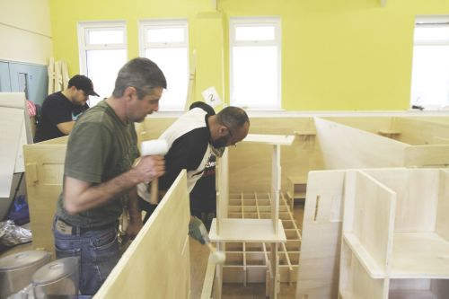 People building wooden sleeping pods