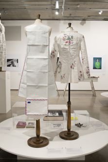 Two mannequins dressed in garments in gallery with portrait photography on the walls