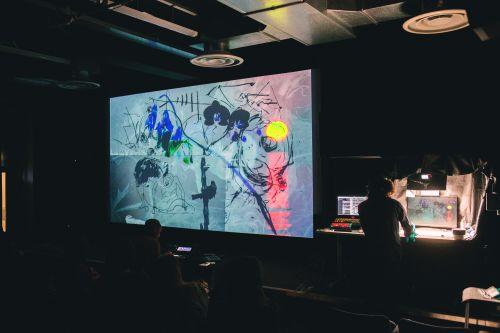 An artist using a screen to exhibit work