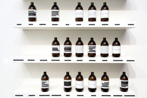 Image of installation of 3 shelves displaying bottles with various labels on them.