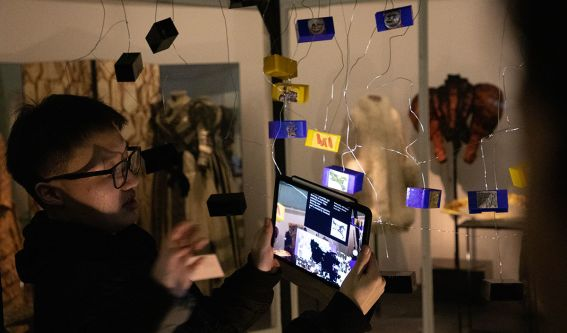 Visitors interact with hanging tablet screens.
