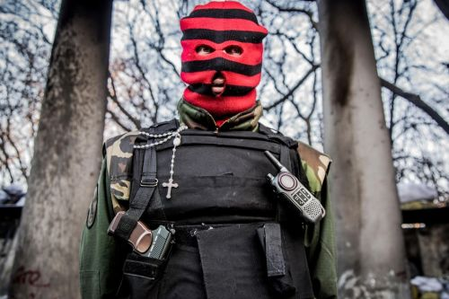 Person in a red and black striped balaclava and bulletproof vest