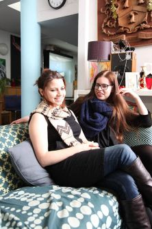 Photo of two female students sitting on a sofa in a communal area in Cordwainers Court