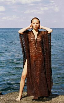 Woman on a rock in a brown seethrough kaftan with the sea behind her