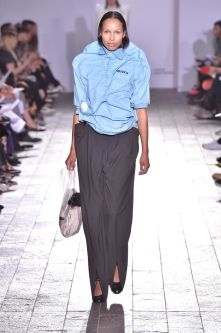 A model walking down a catwalk wearing a blue shirt which goes up the model's chin and a dark grey full length skirt