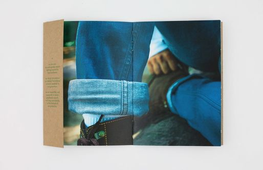 Fashion branding project, showing a double-page magazine spread. The close-up shot of an ankle with rolled-up blue jeans and the top of a black boot.