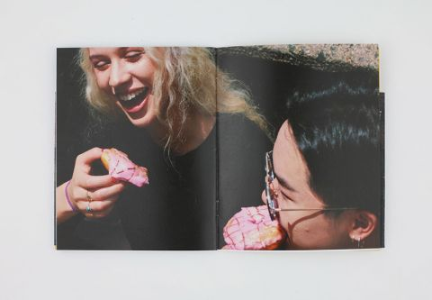 Double-page spread in a magazine, showing a photograph of two people laughing in the sunlight as they share a pink donut.