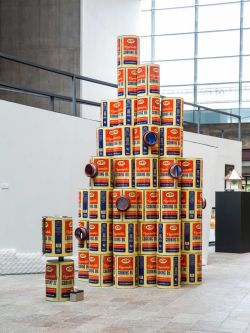 Industrial sized tins of cooking oil stacked to create a large installation