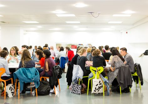 Photograph of the Industry Mentoring Scheme event 2018 at London College of Communication, showing a room full of people engaged in discussions with each other.