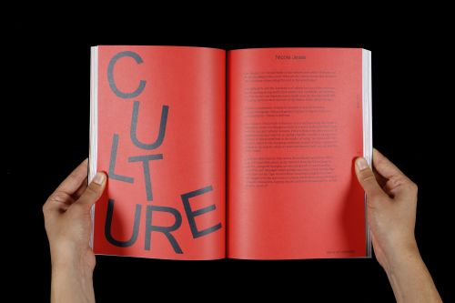 Two hands holding an open publication with red images the word culture spelt out.