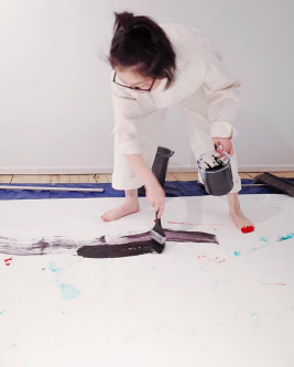 Image of a female student wearing white painting overalls standing barefoot on a large run of paper whilst painting