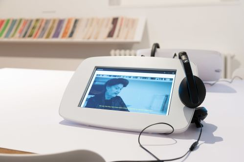 A screen with a pair of headphones hung on the side
