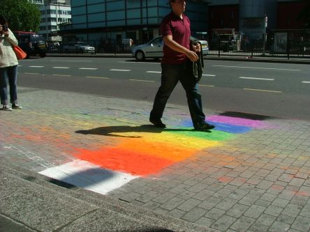 A man walks over a rainbow coloured chalk drawing on a pavement.