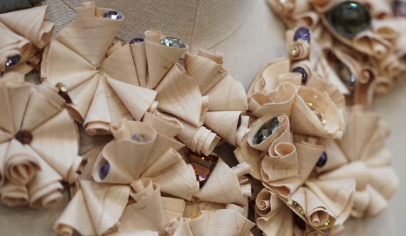 Sustainable neckpiece created from wood shavings and repurposed Swarovski crystals