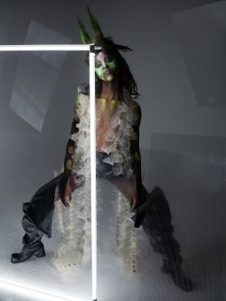 Female model wearing mesh black and white knitted outfit behind a neon white light