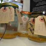 Photograph of a collection of jars with a small amount of honey-like liquid in the bottom, each one has a brown paper tag tied around the top