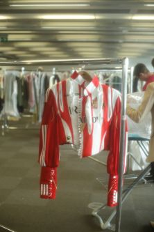 Red and white biker jacket hanging up backstage