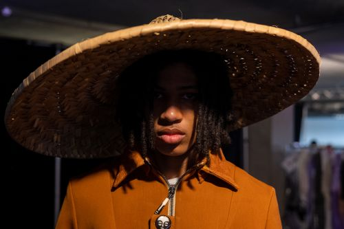 Male model wearing a large straw hat and orange jacket