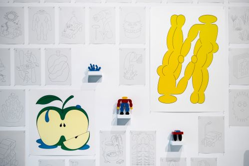 A print of an apple next to a print of two yellow figures